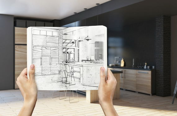 hands holding kitchen blueprint, comparing to real layout in the background